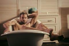 Остальные после работы Мачо ослабьте нагое в ванне в ванной комнате стоковые фото