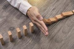 Останавливать деревянное домино блока концепция предотвращает и решение стоковое изображение