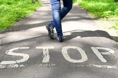 Остановите знак покрашенный на дороге и женских ногах Стоковое Изображение RF