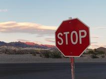 Остановите знак с предпосылкой захода солнца над горами пустыни Стоковое фото RF