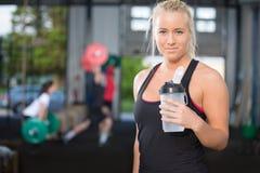 Остатки и питьевая вода женщины на спортзале фитнеса Стоковые Фотографии RF