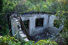 Остатки, который сгорели дома в древесинах над взглядом Стоковая Фотография