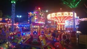Остатки людей в парке атракционов на времени раннего вечера Carousel и поезд детей на предпосылке стоковое изображение