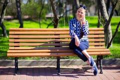 Остатки молодой женщины на скамейке в парке и беседа телефоном Стоковое фото RF