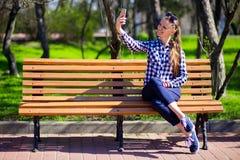 Остатки молодой женщины на selfie скамейки в парке и взятия Стоковая Фотография RF