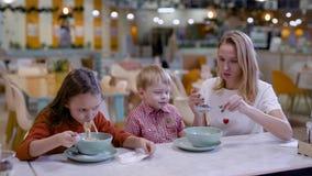 Осторожная молодая мать кормит ее маленький сына спагетти в кафе семьи, preschooler дочь ест сток-видео