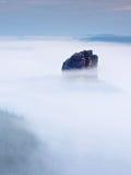 Острая империя утеса песчаника вставляя вне от густого тумана Глубокая туманная долина Стоковое Изображение