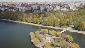 Остров в озере в парке во взгляде городка от трутня видеоматериал