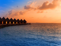 Остров в океане, overwater вилл заходе солнца вовремя. Стоковая Фотография