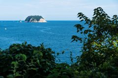 Остров луны Munseom с следом корабля в океане на Согвипхо, острове Jeju, Корее Стоковые Фото