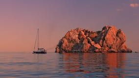 Остров, море, яхта на заходе солнца Стоковые Изображения