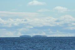 остров на горизонте, облака над морем, живая природа севера Стоковая Фотография