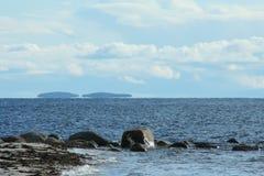 остров на горизонте, облака над морем, живая природа севера Стоковые Изображения
