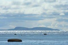 Остров на горизонте, облака над морем, живая природа севера Стоковое Изображение
