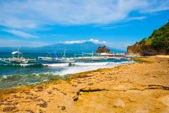 Остров Apo, Филиппины, взгляд на линии пляжа острова Пальмы, утесы, море и шлюпки Стоковые Изображения
