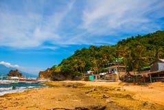 Остров Apo, Филиппины, взгляд на линии пляжа острова Пальмы, утесы, море и шлюпки Стоковое Изображение