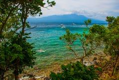 Остров Apo, Филиппины, взгляд от верхней части: море, гора и шлюпки Стоковые Фотографии RF