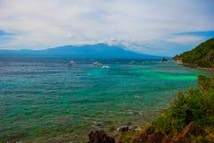 Остров Apo, Филиппины, взгляд от верхней части: море, гора и шлюпки Стоковая Фотография