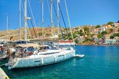 ОСТРОВ SYMI, ГРЕЦИЯ, 25-ОЕ ИЮНЯ 2013: Взгляд на красивых классических белых яхтах, греческий морской порт, дома пряника на холмах Стоковое Изображение