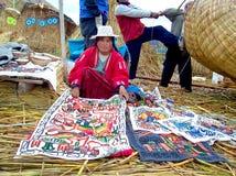ОСТРОВ UROS - ОЗЕРО TITICACA - ПЕРУ, 3-ье января 2007: Неопознанная женщина Uros с ремеслами в традиционном платье Стоковые Фото