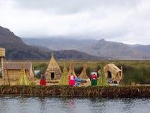 ОСТРОВ UROS - ОЗЕРО TITICACA - ПЕРУ, 3-ье января 2007: Плавая острова Uros на озере Titicaca Неопознанные женщины Uros Стоковые Фотографии RF