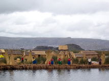 ОСТРОВ UROS - ОЗЕРО TITICACA - ПЕРУ, 3-ье января 2007: Плавая острова Uros на озере Titicaca, Перу Неопознанные женщины в traditi Стоковое Фото