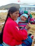ОСТРОВ UROS - ОЗЕРО TITICACA - ПЕРУ, 3-ье января 2007: Плавая острова Uros на озере Titicaca Неопознанные женщины и младенец Uros Стоковая Фотография