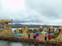 ОСТРОВ UROS - ОЗЕРО TITICACA - ПЕРУ, 3-ье января 2007: Плавая острова Uros на озере Titicaca Неопознанные женщины Uros Стоковая Фотография