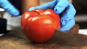 Острое лезвие отрезало в половинном зрелом красном томате на деревянной доске акции видеоматериалы