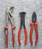 Острозубцы, регулируемый ключ, плоскогубцы на серой конкретной предпосылке Взгляд сверху Стоковые Фото