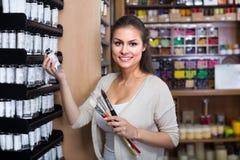 Острокомедийная женщина выбирая различный цвет в трубке Стоковые Изображения