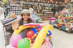Острокомедийная усмехаясь малая дама среди игрушек в супермаркете стоковое фото rf