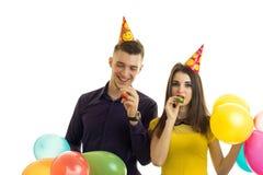 Острокомедийные очаровательные рожки дуновения парня и девушки держат шарики и празднуют день рождения Стоковое Фото