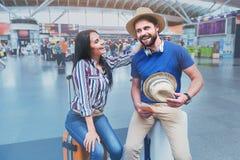 Острокомедийные усмехаясь пассажиры имея потеху в авиапорте Стоковые Изображения