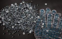 Острые винты в перчатках здания на черной предпосылке стоковое изображение