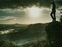 Острый край с человеком наблюдая над туманной и туманной долиной утра к холодному Солнцу спрятанной в облаках стоковое изображение