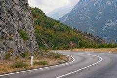 Острый поворот дороги с знаком падая камней Балканы, m Стоковые Изображения RF