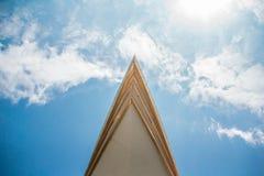 Острый шпиль построения режет до конца облака стоковые фото