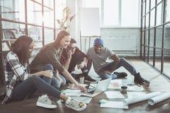 Осчастливленные коллеги используют компьютер в офисе Стоковая Фотография
