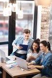 Осчастливленный человек и 2 девушки сидя на деятельности таблицы Стоковое фото RF