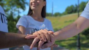 Осчастливленные волонтеры стоя совместно в парке видеоматериал