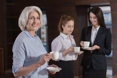 Осчастливленные коллеги выпивая кофе совместно в офисе Стоковые Изображения