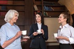 Осчастливленные коллеги тратя перерыв на чашку кофе в офисе Стоковая Фотография RF