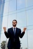Осчастливленный бизнесмен поднимая его оружия в победе вне офисного здания стоковая фотография rf