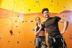 Осчастливленный человек и женщина представляя в взбираясь спортзале Стоковое фото RF