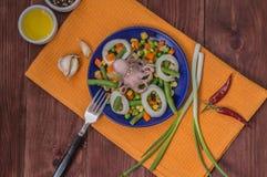 Осьминог и кальмар звенят на свежих овощах голубая плита деревянная предпосылка Взгляд сверху Конец-вверх Стоковая Фотография RF