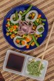 Осьминог и кальмар звенят на свежих овощах голубая плита деревянная предпосылка Взгляд сверху Конец-вверх Стоковые Фотографии RF