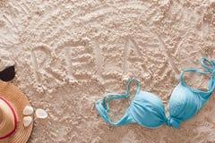 Ослабьте написано в песочном тропическом пляже Стоковая Фотография