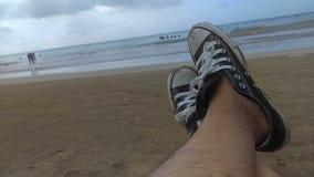 Ослабьте на пляже с тапкамиConverseСтоковое фото RF