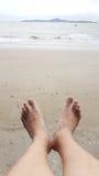 Ослабьте ног человека выше влажный пункт пляжа к морю Стоковое Фото